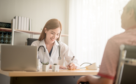 young female Asian doctor smiling cheerfully talking to her patient during medical appointment communication interaction friendly helpful supportive assistance medicine clinical