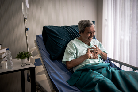 Uomo maturo con dolore al petto che soffre di infarto nel letto d'ospedale.