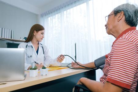 Kobieta lekarz sprawdzanie ciśnienia krwi ff pacjenta starszego mężczyzny