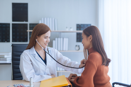 Asian woman doctor examining woman in a hospital Stock Photo
