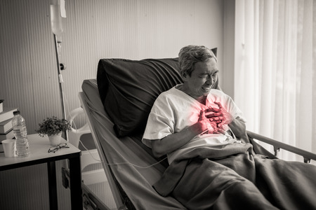 Mature man with chest pain suffering from heart attack in hospital bed.