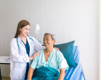 Beautiful Asian doctor taking care of senior patient in hospital bed Stock Photo