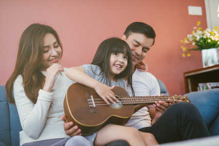 Happy family with guitar at home. Parent see daughter playing guitar