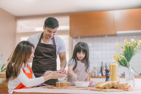 Daughter and parent  preparing the bake 스톡 콘텐츠 - 115385655