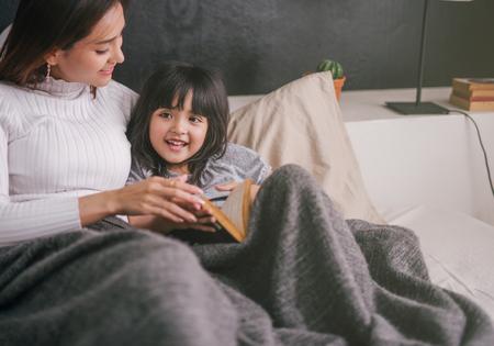 madre e hija leyendo un libro en casa en el dormitorio