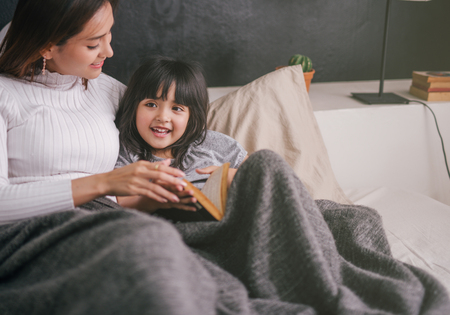 mother and daughter reading book at home in the bedroom Stock Photo