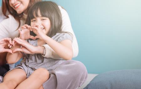 Kleines Mädchen, das Herzform macht, sitzt im Schoß der Mutter.