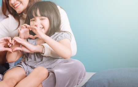 little girl making heart shape sit in mom lap. Stock Photo
