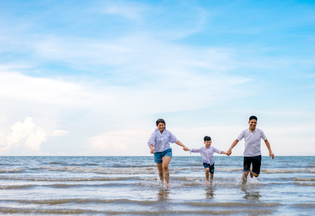 portrait happy family mom dad and son playing together in beach sea side Archivio Fotografico - 115387763