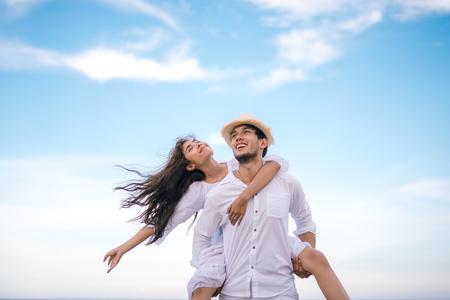 Glückliches entspannendes Paar verliebt in den Strandsommerferien. Frohes Mädchen, das auf jungem Freund huckepack trägt und Spaß hat.