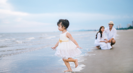 Parent see daughter playing  on the beach. girl playing with family