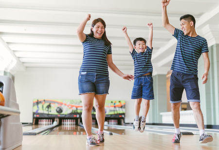 Asian family having fun at bowling club Imagens