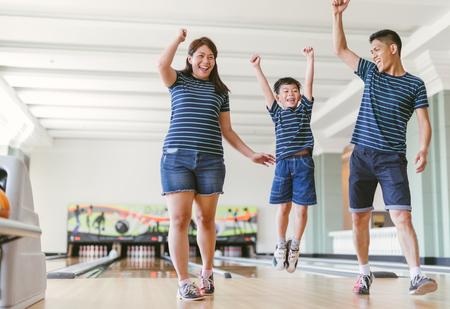 Famille asiatique s'amusant au club de bowling