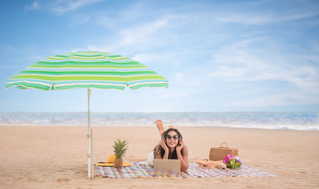 Asian woman relaxing and listening to music  headphone form laptop smartphone, lying on Beach Mat in the beach.