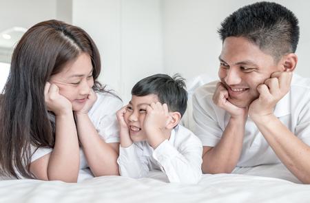 ้portrait happy family mom dad and son  smiling in bed room. look at each other.