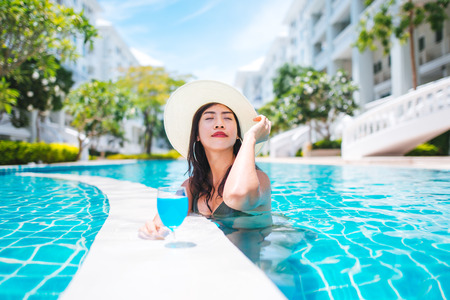 Asian woman in bikini and hat, enjoying cocktail in a swimming pool, summer time