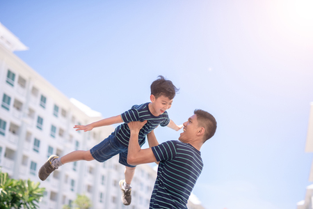 Happy father and son playing together having fun outside the Condominium or apartment building.