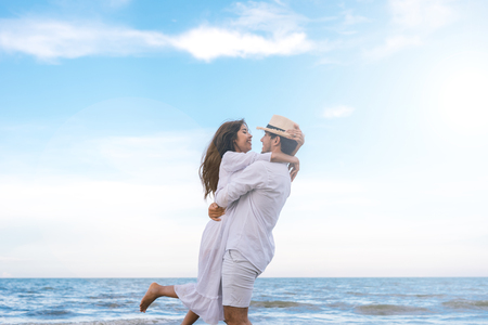 couple in love on beach summer vacations. Joyful girl hugging on young boyfriend