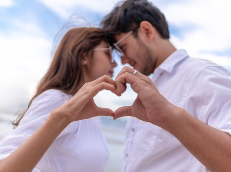 couple making heart shape with hands focus on hand.