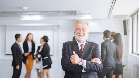 Glücklicher Geschäftsmann auf dem Hintergrund des Geschäftsteams, das Daumen nach oben zeigt