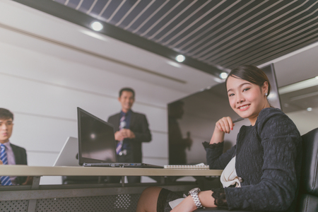 Young Asian businesswoman sitting at a boardroom and smiling at the camera in a boardroom with colleagues in the background. Imagens