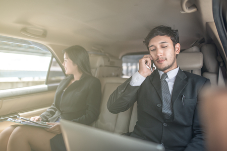 Handsome businessman and his secretary businesswoman talking with phone sitting with laptop on the backseat of the car. Imagens