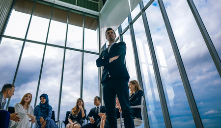 Successful businessman standing with her staff in background at modern bright office