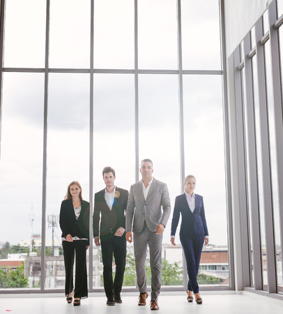 Full length portrait of group of business people walking the corridor in office together Imagens