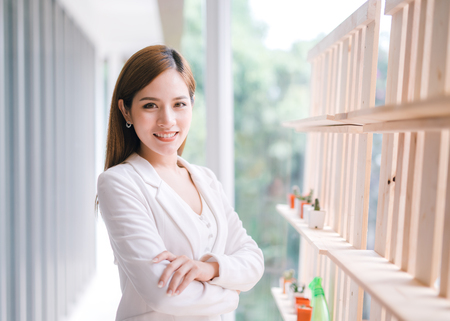 Smiling young Asian businesswoman with arms crossed. Imagens