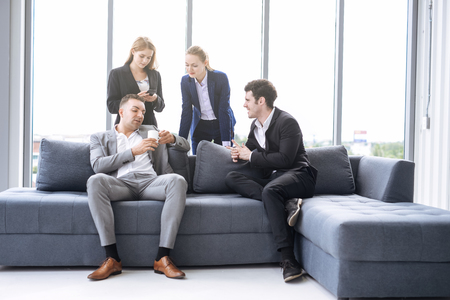business people taking to each other on sofa in office Imagens