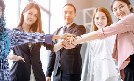 Business people in team stack hands together as unity and teamwork in office. young Asian businessman and group togetherness collaboration Imagens - 119506164