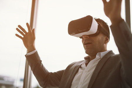 excited businessman in vr headset sitting in office