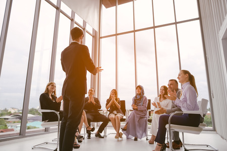 Businessman speaker giving a talk at business meeting. Audience in conference room. Imagens