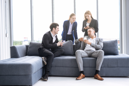 business people taking to each other on sofa in office 写真素材