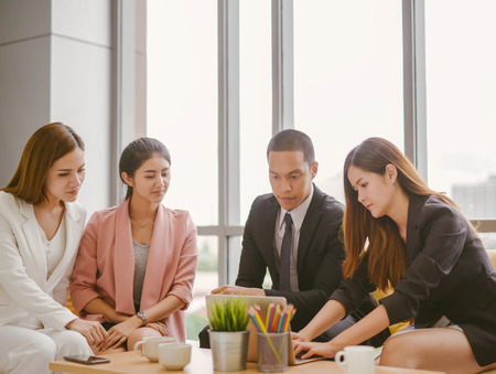 Asian businessmen and businesswoman discussing work sitting at conference table in office.