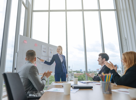 business woman having business meeting with his staff. showing presentation on flip chart or magnetic desk Imagens