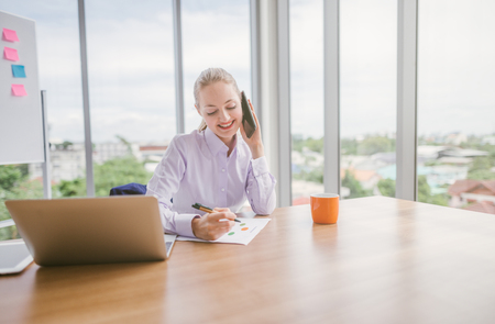 Woman working on laptop at office while talking on phone, businesswoman portrait Imagens