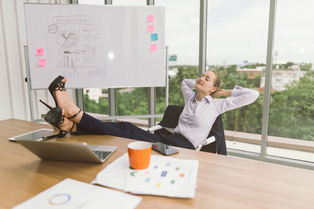 businesswoman relaxing with feet up at desk in creative office . relax and resting Imagens
