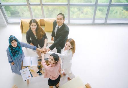 Bovenaanzicht van zakenmensen in team stapelen handen samen als eenheid en teamwerk op kantoor. jonge Aziatische zakenman en groepssaamhorigheidssamenwerking