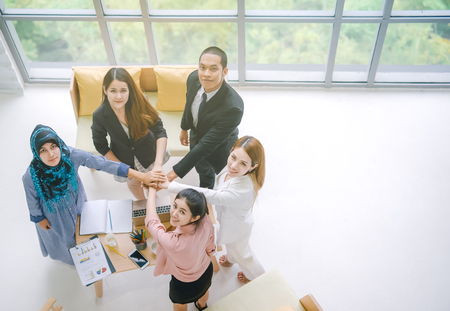 Top view of Business people in team stack hands together as unity and teamwork in office. young Asian businessman and group togetherness collaboration Standard-Bild