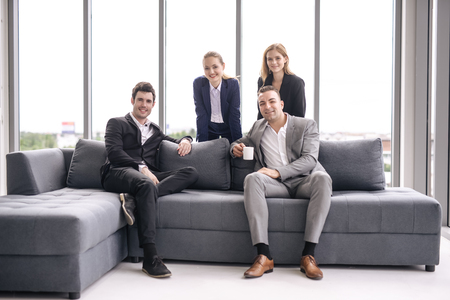 Portrait business people in office sitting on sofa smiling Imagens