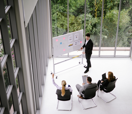 businessman having business meeting with his staff. showing presentation on flip chart.