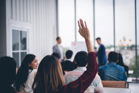 Woman raised up hands and arms  in seminar class room to agree with speaker at conference seminar meeting room
