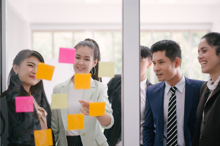Business people meeting at office and explaining to colleagues over sticky notes in office brainstorm strategy workshop