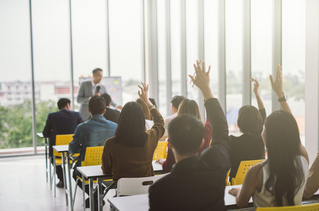 Raised up hands and arms of large group in seminar class room to agree with speaker at conference seminar meeting room Imagens - 119503180
