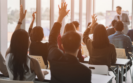 Raised up hands and arms of large group in seminar class room to agree with speaker at conference seminar meeting room