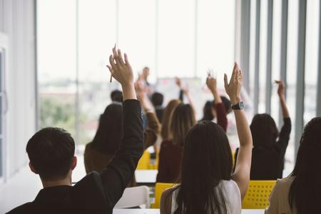 Podniesione ręce i ramiona dużej grupy w sali seminaryjnej na Konferencji