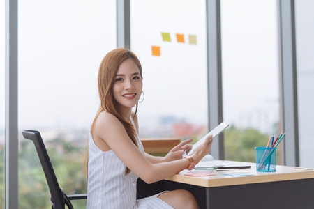 Young Asian business woman working with digital tablet in office Imagens - 119503921