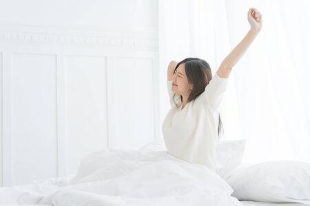 Jonge Aziatische vrouw in de ochtend strekt ze zich uit in haar bed in de slaapkamer Stockfoto