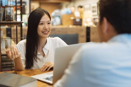 Young Asian woman sitting in cafe talking and having a meeting.